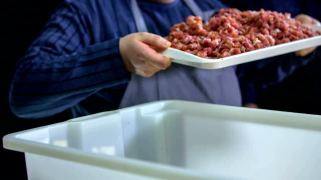 Putting grinding meat in a big container video