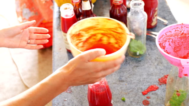 putting homemade sauce in glass bottle- South of Italy video