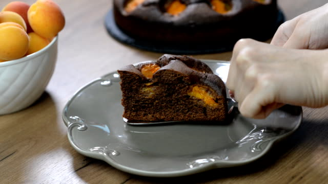 Putting in a plate a piece of chocolate cake with apricots video