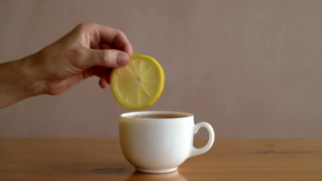 Putting lemon into a cup of tea video