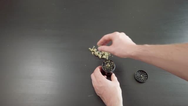 att sätta marijuana i en drog kvarn att mala juridiska läkemedel marijuana, uppifrån och ned, 4k manliga händer. - thc bildbanksvideor och videomaterial från bakom kulisserna