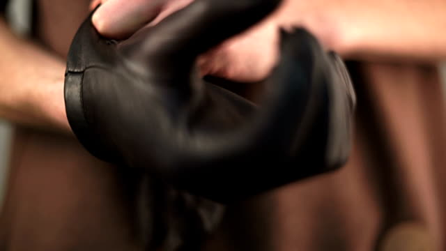 Putting on old leather gloves video