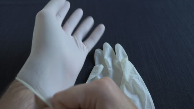 putting on surgical white gloves - guanto indumento sportivo protettivo video stock e b–roll