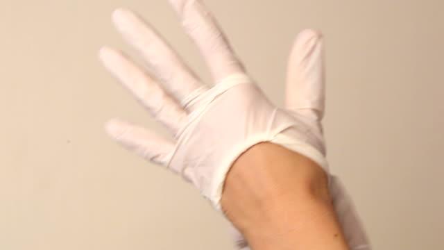 vídeos y material grabado en eventos de stock de putting en guantes médicos blanco - guante quirúrgico