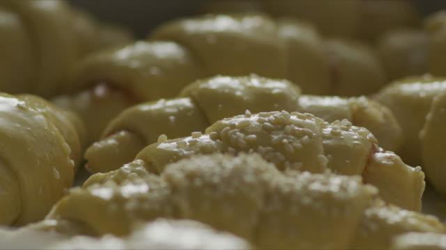 vidéos et rushes de putting sesame seeds sur croissant brut - vidéo stock - pâtisseries et feuilletés
