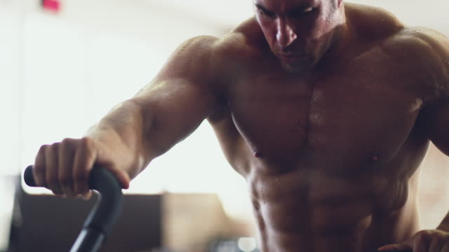 Putting those muscles to work 4k video of a muscular young man working out on an exercise bike in the gym macho stock videos & royalty-free footage