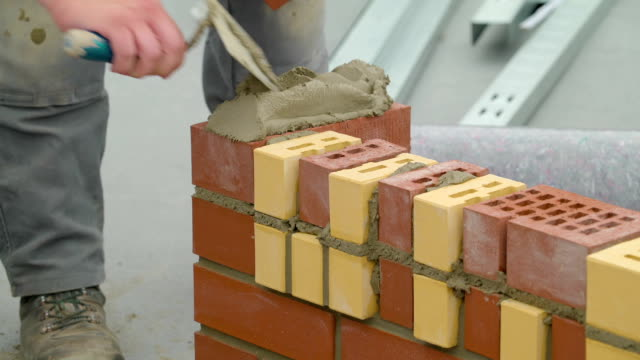 Putting up a cement on the red brick in Ireland video