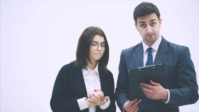 Puzzled business partners holding clipboard with sheet of paper and question mark written on it. They don't understand what it means.