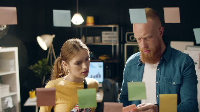 Puzzled guy asking female colleague for advice in business hipster office.