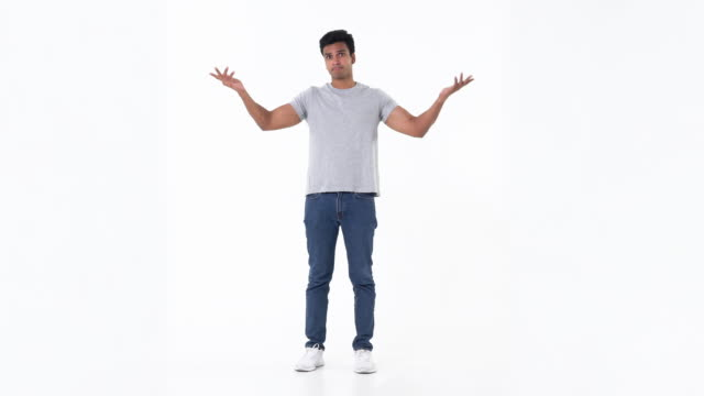 Puzzled handsome young Indian man in plain blue jeans Portrait of puzzled and confused handsome young Indian man in plain blue jeans and grey t-shirt shrugging his shoulder on white background full length stock videos & royalty-free footage