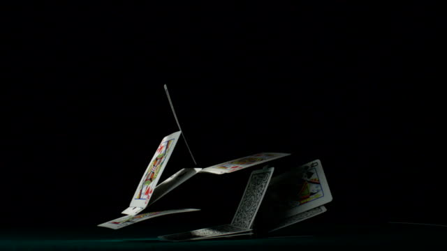 Pyramid house of playing cards falling down, Slow Motion video