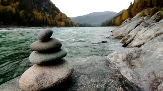 Pyramid of stones on mountain river in Altay, Russia video