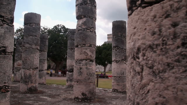Pyramids and stone columns of Mayan city Dolly shot of the old stone columns in Chichen Itza. Pyramid in the background architectural column stock videos & royalty-free footage