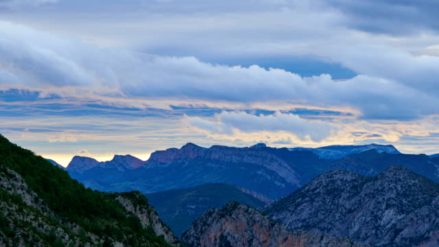 Pyrenees time lapse - Clouds running fast in summer Clouds over Coll de Nargó's mountains running fast in sunset. Catalonia. lleida stock videos & royalty-free footage