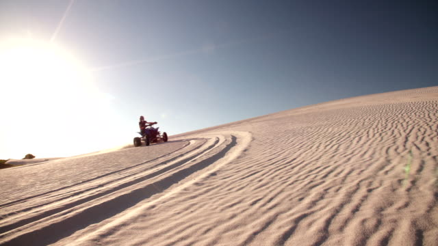 Quad racer driving up a sand dune with sun flare video
