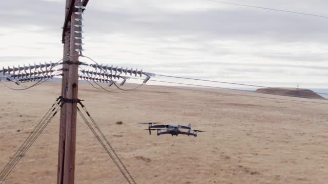 vídeos y material grabado en eventos de stock de un dron quadcopter inspecciona las líneas eléctricas con un campo de hierba marrón debajo de un cielo parcialmente nublado - drone footage