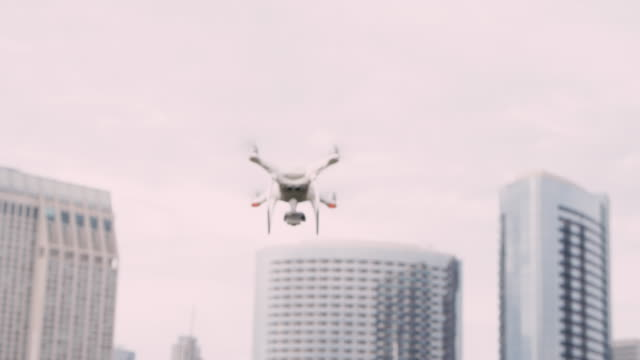 Quadcopter drone with camera on gimbal flying in the city sky, shot in slow motion Slow motion isolated shoot of drone flying in air with cityscape in background scientific imaging technique stock videos & royalty-free footage