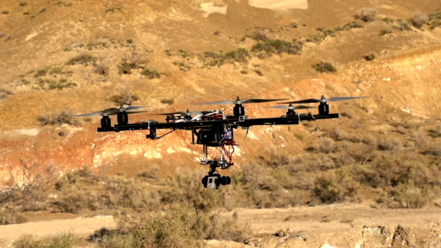 Quadcopter Explores Desert Canyon Easy drone hovered over the desert against the backdrop of the hills. Slow Motion at a rate of 480 fps quadcopter stock videos & royalty-free footage