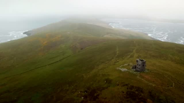 4K quadrocopter flies out of the clouds. In the process the old signal tower on Dursey Island becomes visible