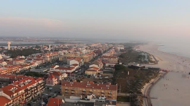 vídeos de stock e filmes b-roll de quaint mediterranean town next to the beach with traffic. barra beach from aveiro, portugal. - aveiro