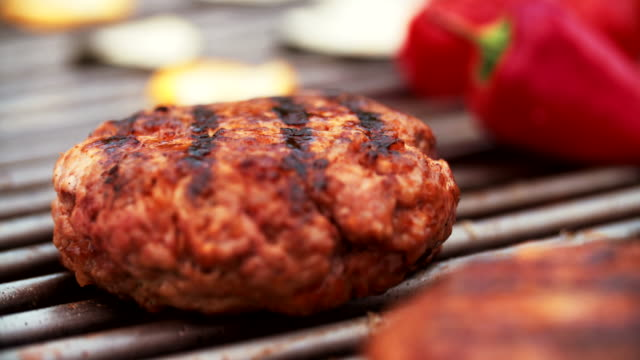 Quality beef patties grilling on a barbecue outdoors video
