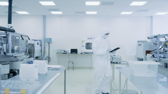 品質管理チェック: 科学者を使用してデジタル タブレット コンピューターと身に着けている防護服製造所を説明します。製品製造: 薬学、半導体、バイオ テクノロジー。 - lab点の映像素材/bロール