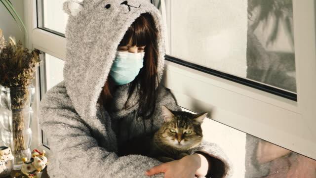 quarantäne. eine frau in einer schützenden medizinischen maske sitzt mit einer katze auf einer fensterbank. - nutztier oder haustier stock-videos und b-roll-filmmaterial