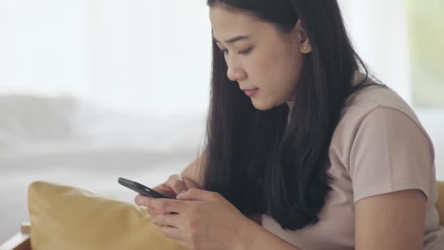 quarantäne zu hause: asiatische frauen nutzen telefon zu hause - smartphone mit corona app stock-videos und b-roll-filmmaterial