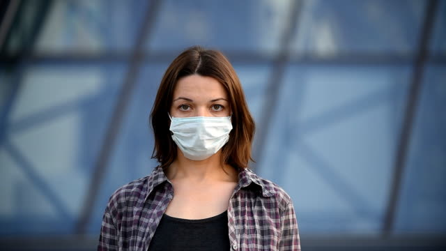 Quarantine Covid-19 End Concept Young woman takes off her face mask and smiles. Modern city background. covering stock videos & royalty-free footage