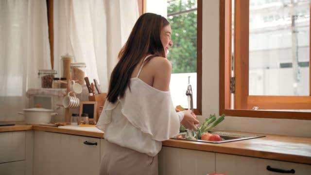 Quarantaine pendant Covid-19 : Jeunes femelles lavant des légumes à la maison - Vidéo