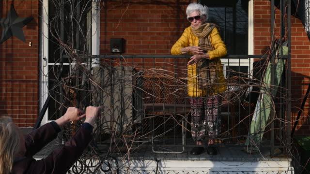 stockvideo's en b-roll-footage met quarantaine eldery woman alone home sociale distantiëring met familie - raam bezoek