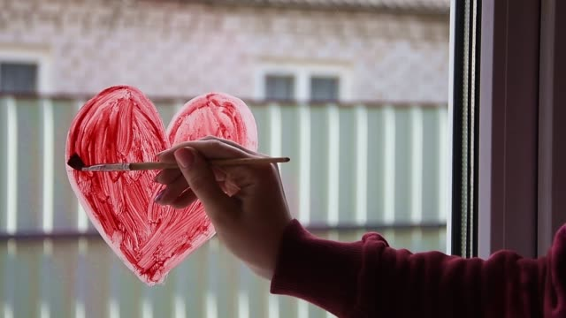 quarantine. female hand draws red heart on the window with paint. waiting for the rainbow, stay home - hand on glass covid video stock e b–roll