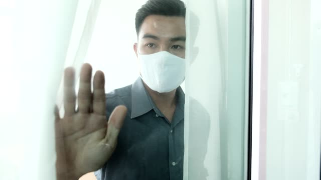 Quarantine self isolation lockdown social distancing at home feeling sad depress wearing protective facemask, world pandemic coronavirus covid-19 looking outside from window curtain, Asian businessman