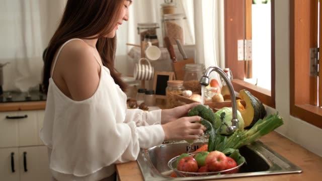 Quarantine : Woman washing vegetables at home