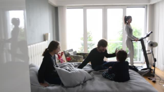 quarantined family at bedroom in the morning. defocused. - cultura del medio oriente video stock e b–roll