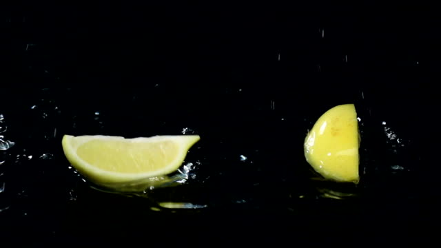 Quarter of lemon falls into the water. Black background. Slow motion video