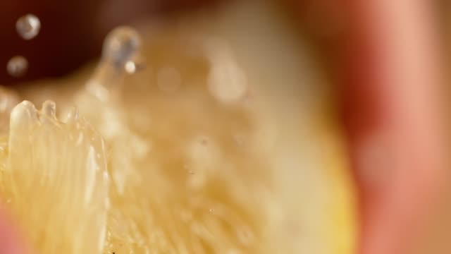 macro, dof: quarter of organic lemon is squeezed and sour juice squirts out. - gusto aspro video stock e b–roll