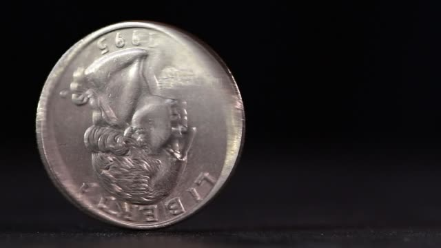 A quarter USD coin spinning on table