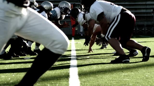 vídeos de stock e filmes b-roll de a quarterback hands off the ball to the running back who goes downfield with it - liga desportiva