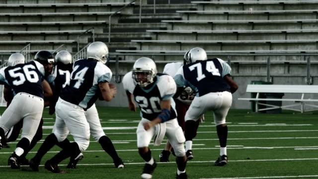 vídeos y material grabado en eventos de stock de un mariscal de campo se encaja a presión la bola y es saqueada por un defensor - fútbol americano