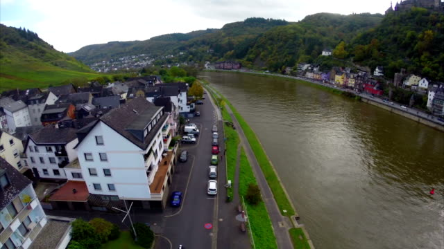 Quay of small village colorful houses, river ships, parked cars. Beautiful aerial shot above Europe, culture and landscapes, camera pan dolly in the air. Drone flying above European land. Traveling sightseeing, tourist views of Germany. video