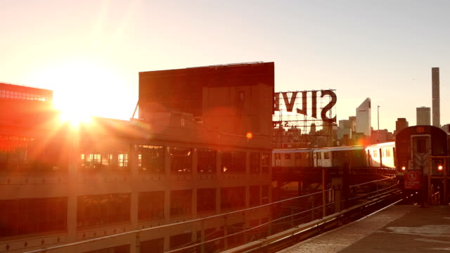 Queensboro Plaza Subway Arrival in New York City Subway arriving with view of the Manhattan skyline during sunset in Queens, New York City. subway platform stock videos & royalty-free footage