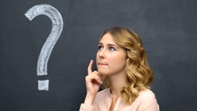 stockvideo's en b-roll-footage met vraagteken geschreven op blackboard, pensieve vrouw denken, besluit nemen - question