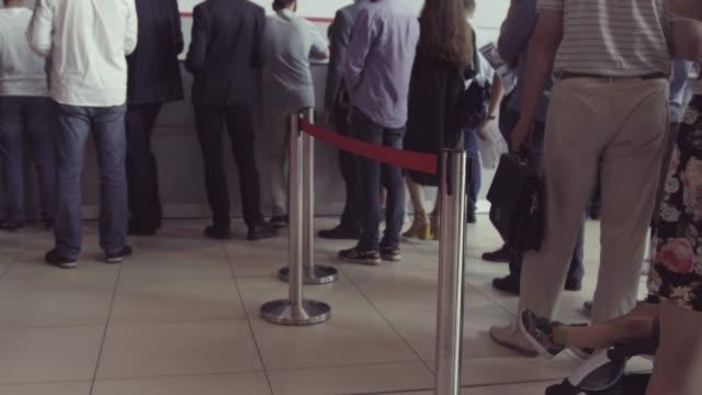 ラインで待機している人々のキューが提供されます。現金に立っている人の列。郵便局、銀行、またはチケット販売代理店である可能性があります - 銀行取引点の映像素材/bロール
