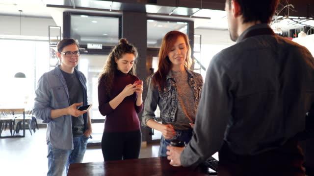 sıra sabah kahve-evde duran ve paket servisi olan restoran içecekler cellphone ile ödeyerek satın gençlerin. modern yaşam tarzı ve temassız ödeme kavramı. - sipariş vermek stok videoları ve detay görüntü çekimi