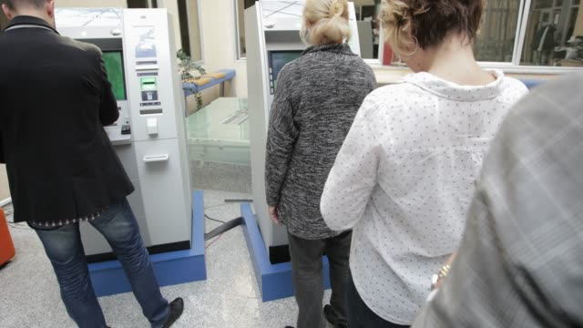Queuing for ATM, handheld shot Two people using ATM machine while two others waiting in line, handheld shot banks and atms stock videos & royalty-free footage