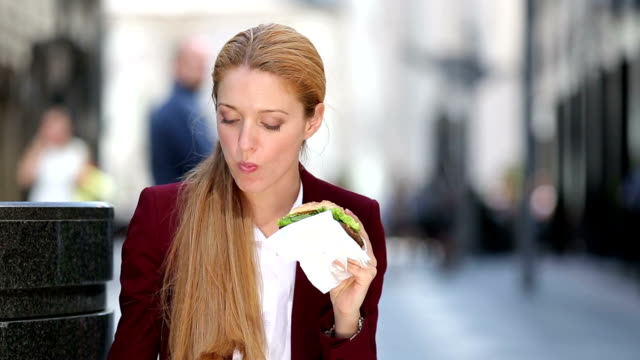 Quick lunch busy woman. A young woman eating a hamburger on a city street. video
