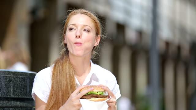Almuerzo rápido mujer de negocios. Una joven mujer comiendo una hamburguesa en una calle de la ciudad. - vídeo