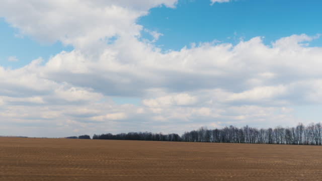 Quickly drive along the plowed field in early spring. Visible agricultural field and blue sky with clouds. POV window plate video, 3 axis stabilized video