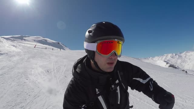 Quickly Skiing To Ski Slopes In The Mountains And A Lot Of Adrenaline In Blood POV closeup selfie portrait of a skier in a helmet and goggles, quickly skiing down the ski slope in the mountains in winter, sun shines into the camera and creates glare, a lot of adrenaline in blood crash helmet stock videos & royalty-free footage